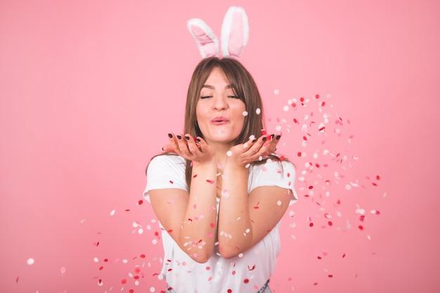 ピンクの上に隔離の手で紙吹雪を保持している美しい笑顔