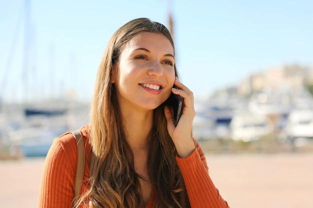 屋外の耳の近くにスマートフォンを保持している美しい笑顔の女の子