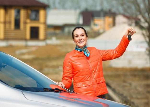 그의 손 자동차에서 키를 들고 아름 다운 웃는 소녀