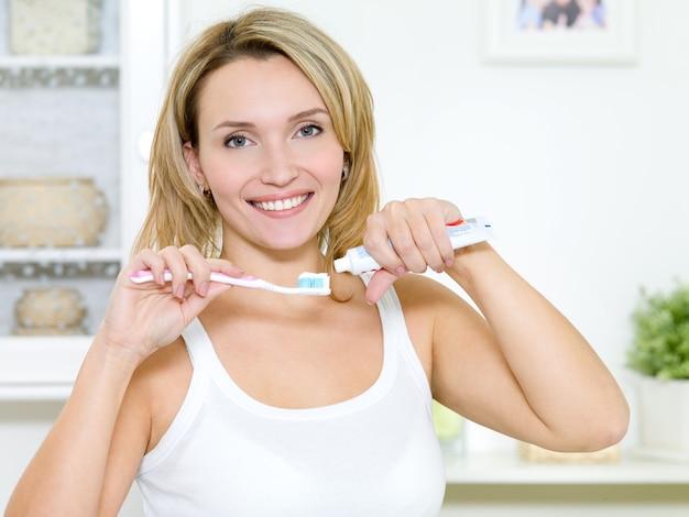 美しい笑顔の女の子は、歯磨き粉で歯ブラシを保持します