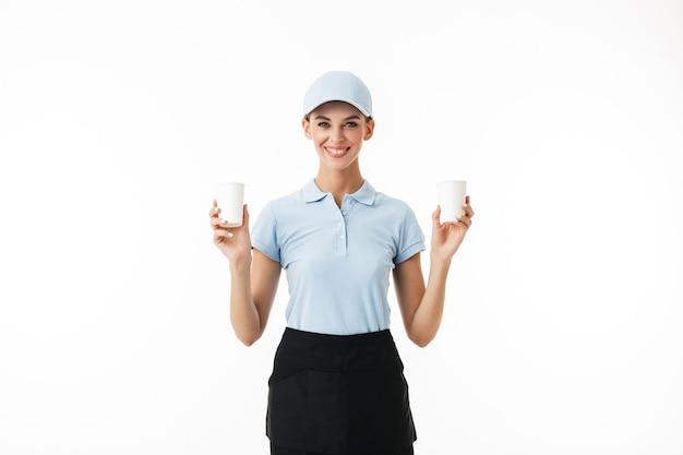 青いポロtシャツとキャップの美しい笑顔の女の子が幸せにしながら水のための使い捨てカップを手に持っています