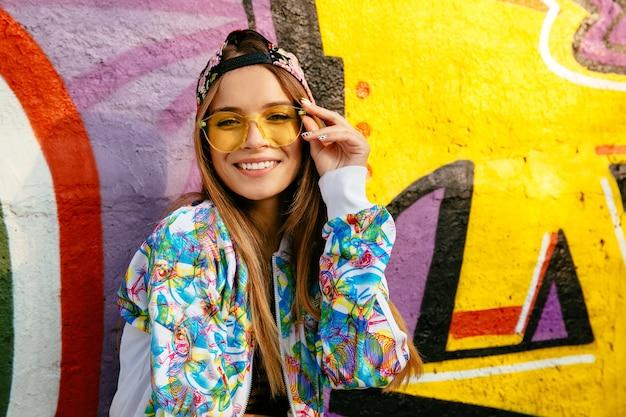 아름 다운 웃는 소녀 안경에 카메라에 포즈. 세련된 재킷과 모자를 입고 있습니다.