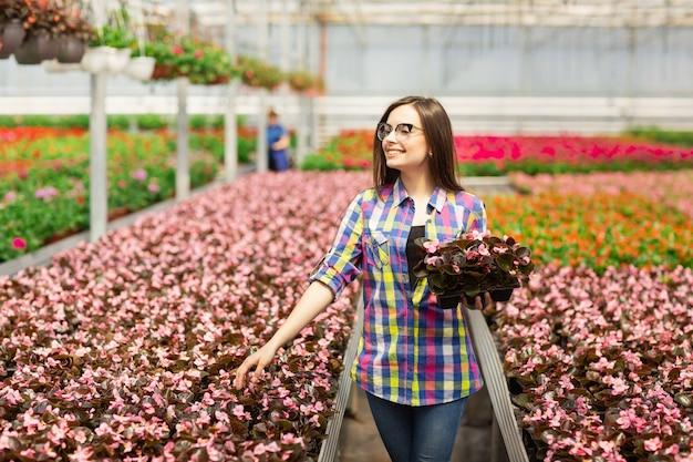 온실, 꽃과 노동자 안경에 아름 다운 웃는 소녀.