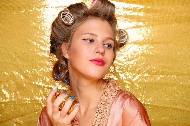 골드에 고립 된 머리카락 curlers에서 아름 다운 웃는 소녀. 젊은 아름 다운 섹시 웃는 여자의 초상화입니다. 향수, 향수 병을 들고 향기 냄새가 젊은 아름다운 소녀 여자
