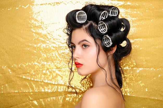 골드에 고립 된 머리 curlers에 아름 다운 웃는 소녀. 젊은 아름 다운 섹시 한 웃는 여자의 초상화