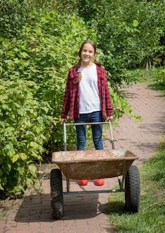 Красивая улыбающаяся девушка в джинсах и рубашке с тачкой в саду