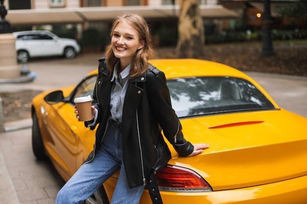 행복하게 동안 손에 갈 커피 한잔 들고 노란색 스포츠 자동차에 기대어 가죽 재킷에 아름 다운 웃는 소녀