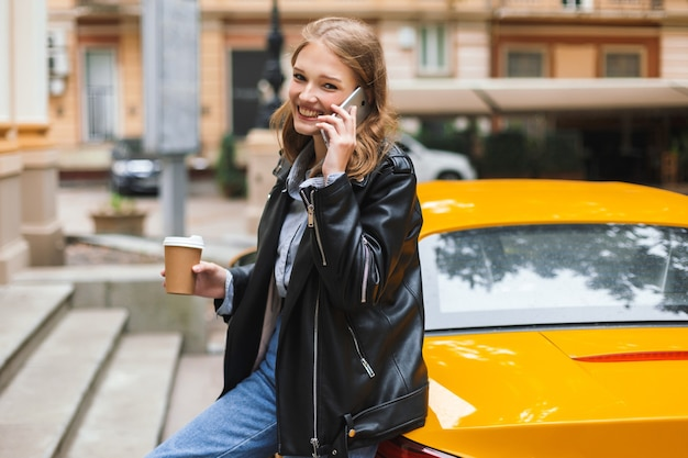 Красивая улыбающаяся девушка в кожаной куртке с чашкой кофе, чтобы пойти, опираясь на желтый спортивный автомобиль, разговаривая по мобильному телефону, пока счастливо