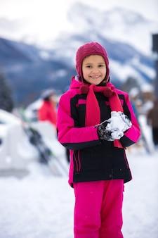 Красивая улыбающаяся девушка в розовом лыжном костюме делает снежок