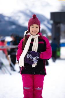 Красивая улыбающаяся девушка в розовом лыжном костюме позирует на фоне высокой горы, покрытой снегом