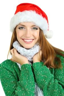 白で隔離されるサンタ帽子の美しい笑顔の女の子