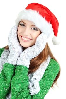 白で隔離のサンタ帽子の美しい笑顔の女の子