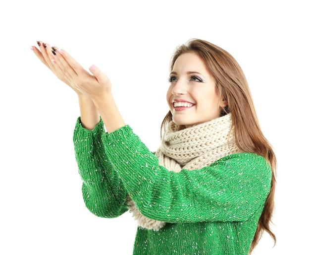 白い壁に分離された暖かいニットスカーフの美しい笑顔の女の子