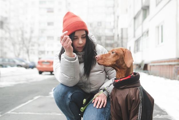暖かい冬の服で美しい微笑の女の子は服を着た犬を保持します