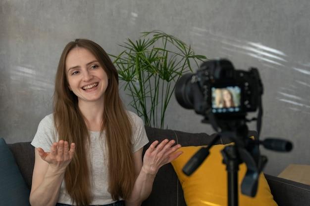 아름다운 웃는 소녀가 비디오 블로그를 위해 자신을 촬영하고 있습니다. 카메라에 자신을 촬영하는 젊은 블로거. 인기있는 취미.