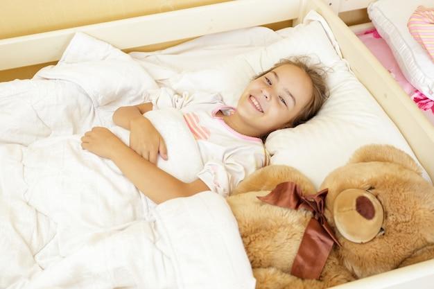 大きなテディベアと一緒にベッドに横になっている笑顔の美しい女の子