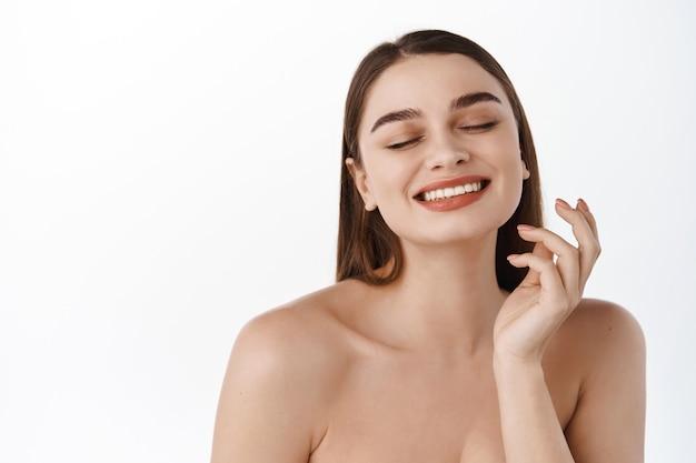 Красивая улыбающаяся девушка-модель с естественным макияжем, трогающая светящуюся увлажненную кожу на белой стене