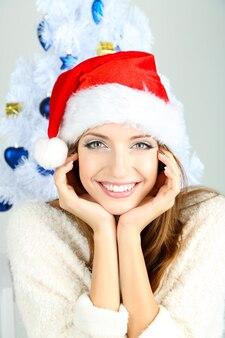 Красивая улыбающаяся девушка возле елки крупным планом