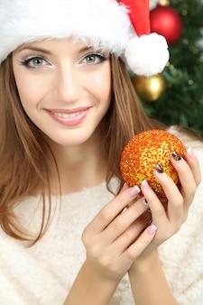 Красивая улыбающаяся девушка возле елки в комнате