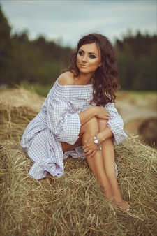Beautiful smiling girl near a hay bale in the countryside. girl sitting on the haystack
