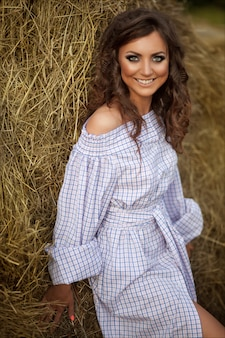 Beautiful smiling girl near a hay bale in the countryside