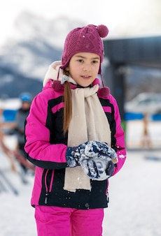 Beautiful smiling girl posing on top mountain covered by snow