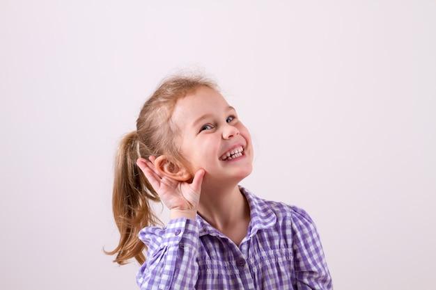 美しい笑顔の女の子は、よく聞くために耳に手を置きます