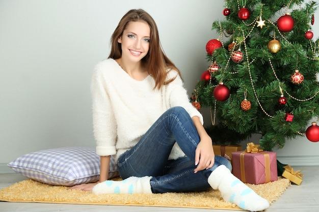 Красивая улыбающаяся девушка сидит возле елки в комнате