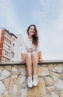 通りの背景に石の壁に座っている美しい笑顔の女の子。街を散歩している長い髪とショートパンツの幸せな女の子。