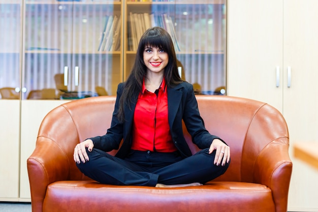 Beautiful smiling girl sitting on a sofa in the lotus position