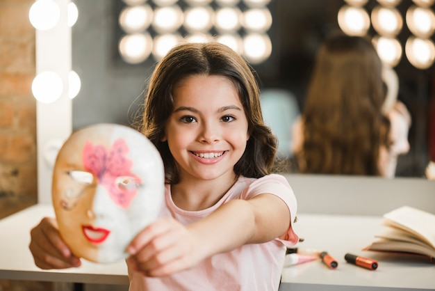 Beautiful smiling girl standing at backstage showing face mask