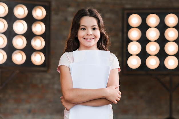 Beautiful smiling girl standing in front of stage light