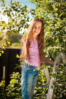 정원에서 사다리에 서있는 아름 다운 웃는 소녀