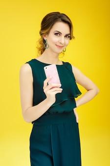 Beautiful smiling girl uses smartphone on yellow background