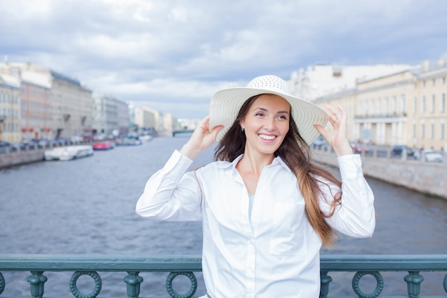 A beautiful and smiling girl in a white hat.