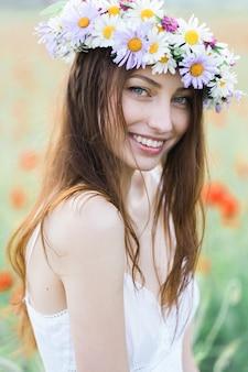 彼女の頭に花の花輪を持つ美しい笑顔の女の子