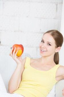 Красивая улыбающаяся девушка с яблоком, сидя дома.