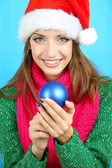 Красивая улыбающаяся девушка с елочным шаром на синем фоне