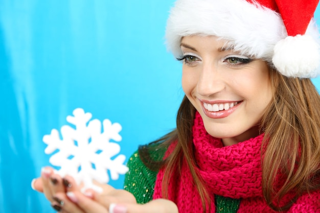 Красивая улыбающаяся девушка с рождественской снежинкой на синем фоне
