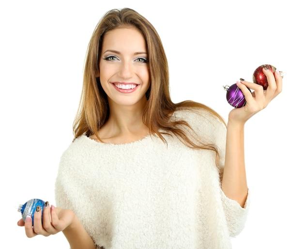 Красивая улыбающаяся девочка с елочными игрушками, изолированными на белом