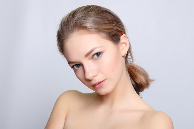 きれいな肌、自然なメイク、灰色の背景に白い歯を持つ美しい笑顔の女の子