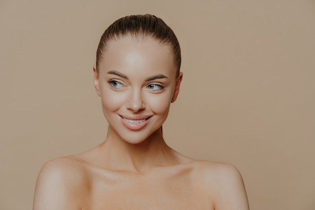 Beautiful smiling girl with clean skin, natural make-up, and white teeth on beige