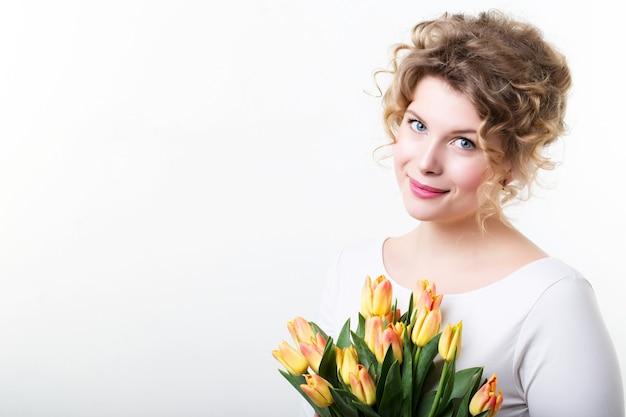 Красивая улыбающаяся девушка с цветами на белом.