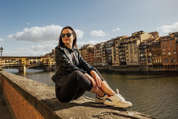 Красивая улыбающаяся девушка в очках во флоренции на фоне старого моста и реки арно.
