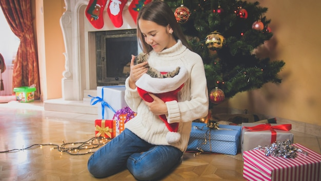 Beautiful smiling girl with kitten sitting under christmas tree