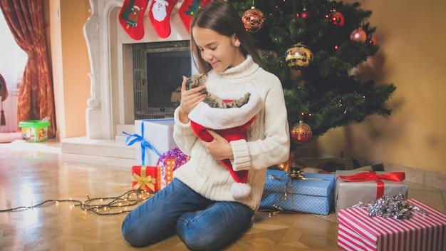 Красивая улыбающаяся девочка с котенком, сидящим под елкой