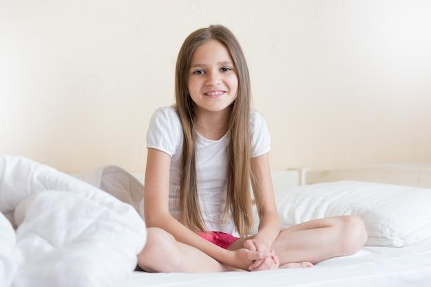침대에 앉아 긴 검은 머리를 가진 아름 다운 웃는 소녀