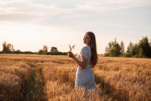 카메라를 다시 바라보는 작은 이삭 꽃다발을 든 아름다운 웃는 소녀