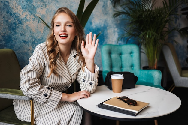 Beautiful smiling girl with wavy hair in striped trench coat happily waving and