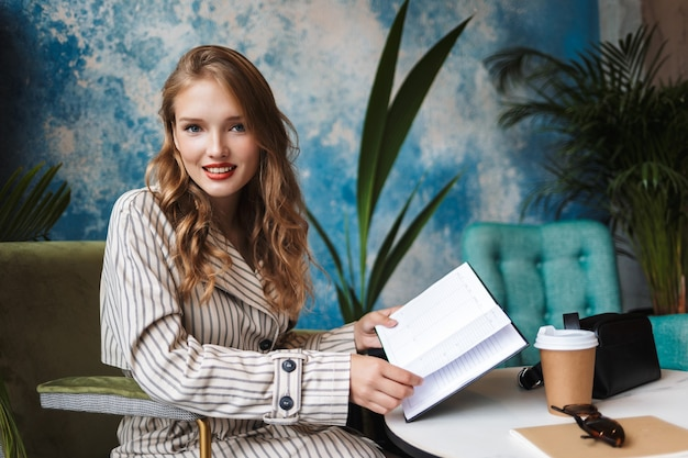 Beautiful smiling girl with wavy hair in striped trench coat holding notebook in hands happily